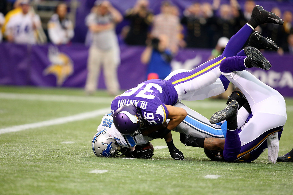 . Reggie Bush #21 of the Detroit Lions is tackled by Robert Blanton #36 and Erin Henderson #50 of the Minnesota Vikings on December 29, 2013 at Mall of America Field at the Hubert H. Humphrey Metrodome in Minneapolis, Minnesota. (Photo by Adam Bettcher/Getty Images)