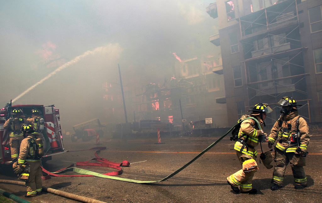 . Houston firefighters work to extinguish a five-alarm fire at a construction site Tuesday, March 25, 2014, in Houston. (AP Photo/Houston Chronicle, Mayra Beltran)
