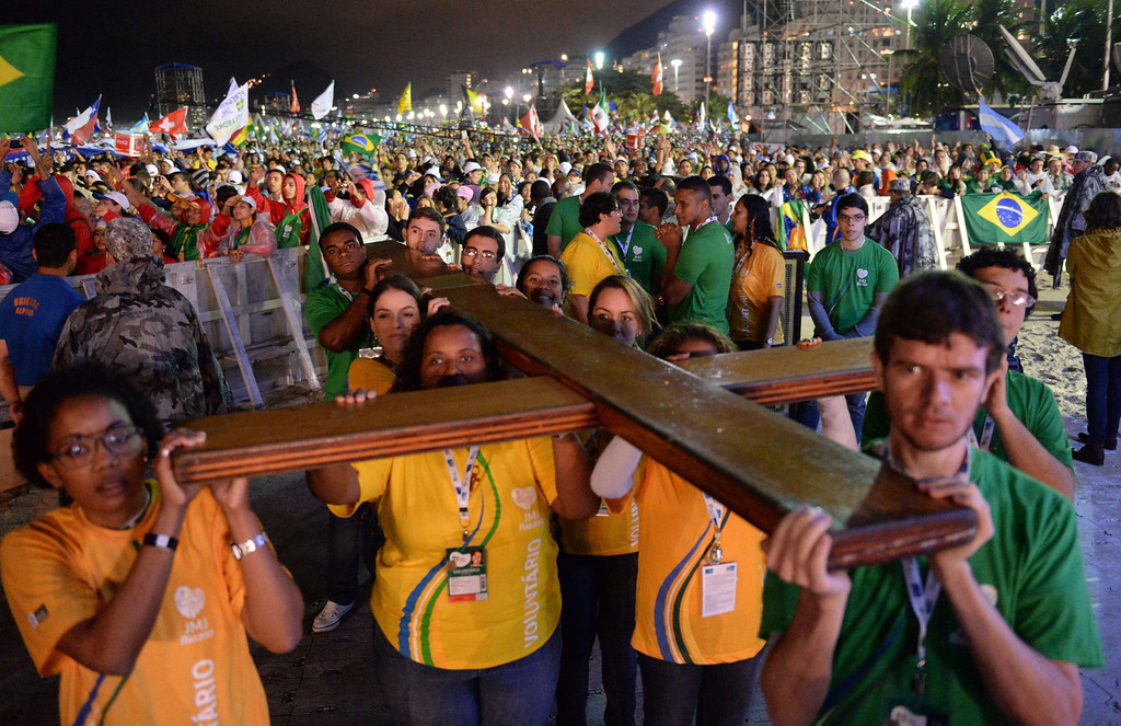 . Catholic faithfuls carry the World Youth Day (WYD) Cross that in 1984 Pope John Paul II entrusted the youth of the world, to the stage before the start of the WYD opening mass, at Copacabana beach in Rio de Janeiro, Brazil, on July 23, 2013. The highlight of the landmark visit of Pope Francis to the world\'s most populous mainly Catholic country will be WYD, a five-day event that kicks off today. Pope Francis\'s popularity on his Latin American home turf posed a challenge to Brazilian authorities Tuesday after adoring crowds mobbed his car on his arrival on Monday.  TASSO MARCELO/AFP/Getty Images