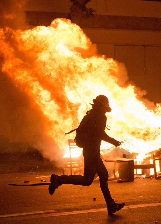 """. Demonstrator runs near a burning barricade after a protest for the \""""Teachers\' day\"""", on October 15, 2013 in Rio de Janeiro, Brazil. AFP PHOTO / CHRISTOPHE  SIMON/AFP/Getty Images"""