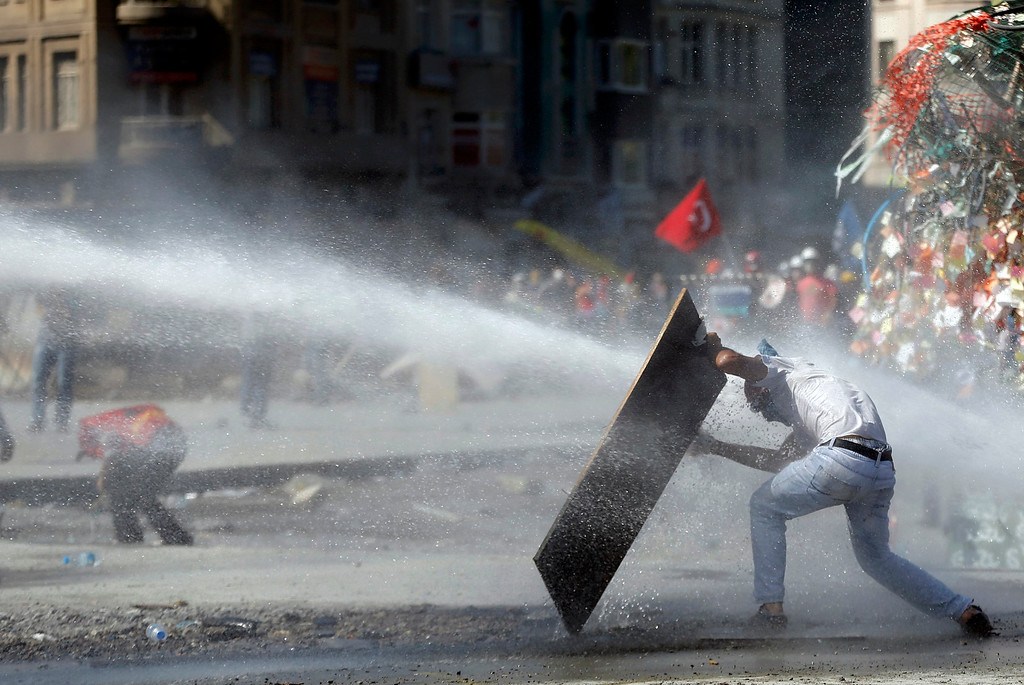 . A protester protects himself from a riot police water cannon during a protest at Taksim Square in Istanbul June 11, 2013. REUTERS/Murad Sezer