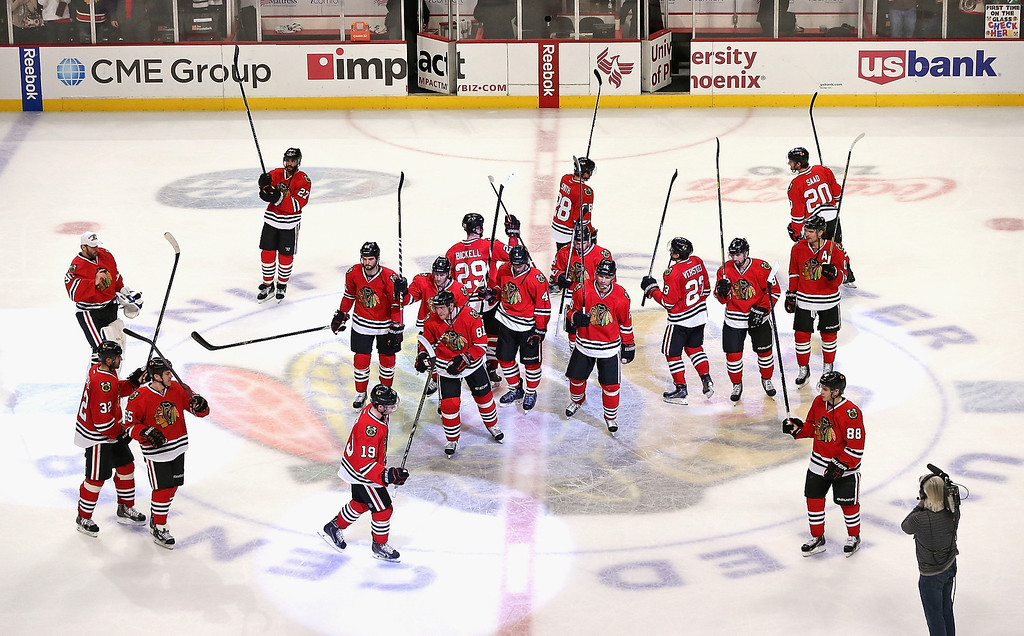 . CHICAGO, IL - DECEMBER 27: Members of the Chicago Blackhawks salute the crowd after a win over the Colorado Avalanche at the United Center on December 27, 2013 in Chicago, Illinois.  The Blackhawks defeated the Avalanche 7-2. (Photo by Jonathan Daniel/Getty Images)