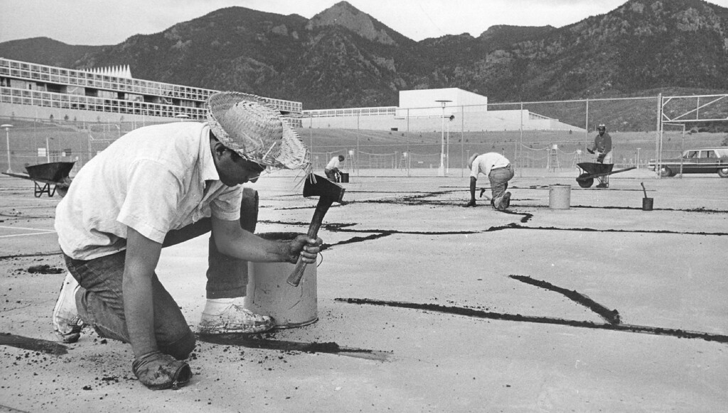 ". Construction worker Frank Macias of Denver repairs the cracks in a tennis court with bitumen cement. Like any ""city,\"" the Air Force Academy has recreation facilities and park areas for the enjoyment of its 10,522 residents.  1965. The Denver Post Library Archive"