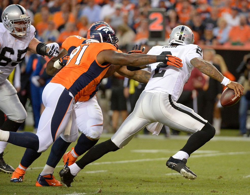 . Denver Broncos defensive end Robert Ayers (91) and Denver Broncos defensive tackle Kevin Vickerson (99) chase Oakland Raiders quarterback Terrelle Pryor (2) out of the pocket in the first quarter. The Denver Broncos took on the Oakland Raiders at Sports Authority Field at Mile High in Denver on September 23, 2013. (Photo by John Leyba/The Denver Post)