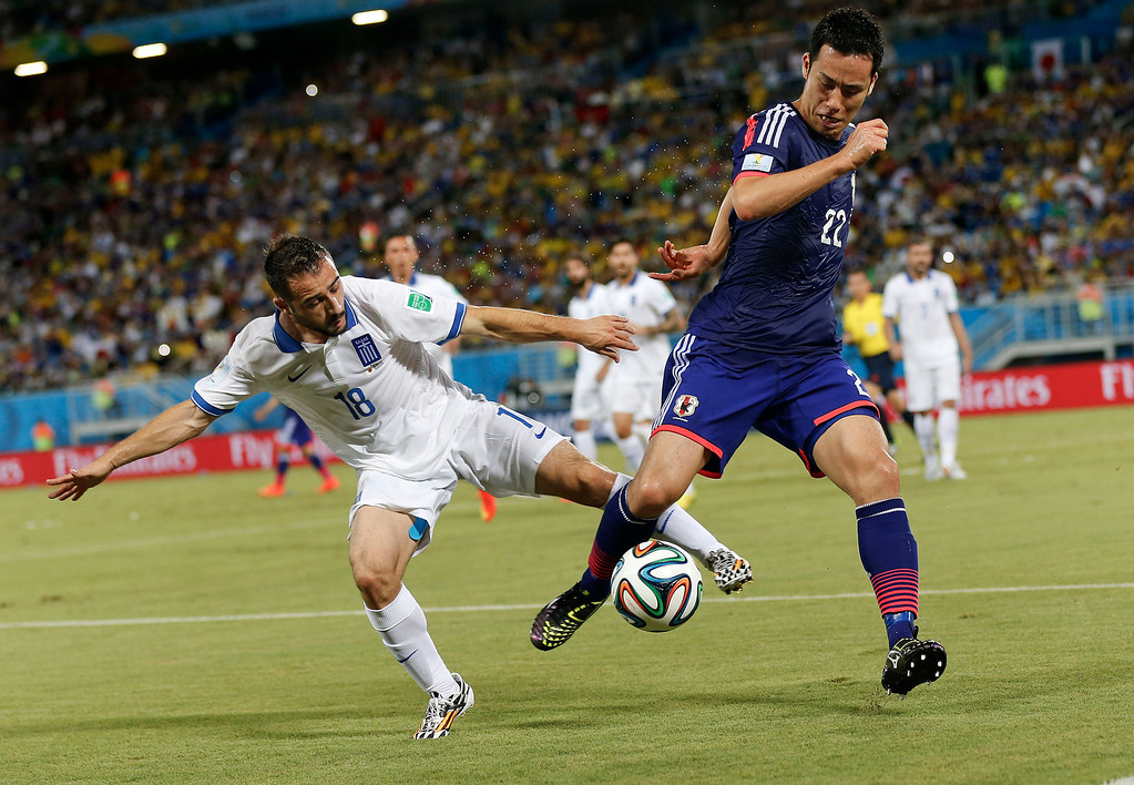 . Greece\'s Giannis Fetfatzidis, left, challenges Japan\'s Maya Yoshida during the group C World Cup soccer match between Japan and Greece at the Arena das Dunas in Natal, Brazil, Thursday, June 19, 2014. (AP Photo/Frank Augstein)