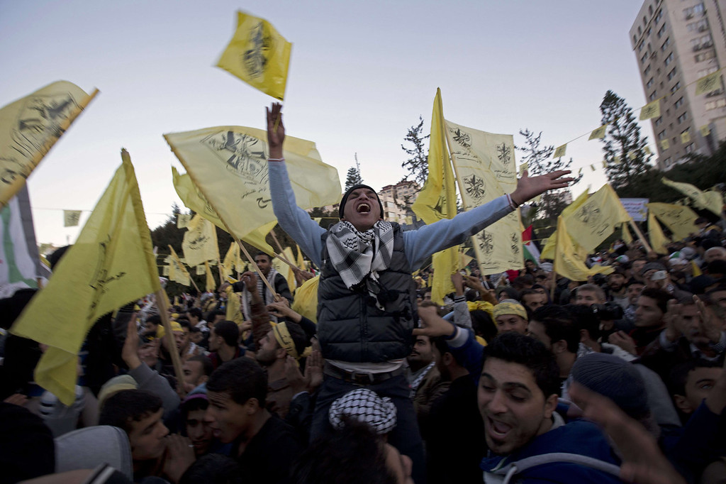. Palestinians waves Fatah movement flags and shout slogans during a rally the day before the 49th anniversary of the formation of the movement in the Unknown Soldier Square in Gaza City on December 31, 2013. The Fatah anniversary commemorates the first operation against Israel claimed by its armed wing then known as Al-Asifa (The Storm in Arabic) on January 1, 1965.  MOHAMMED ABED/AFP/Getty Images