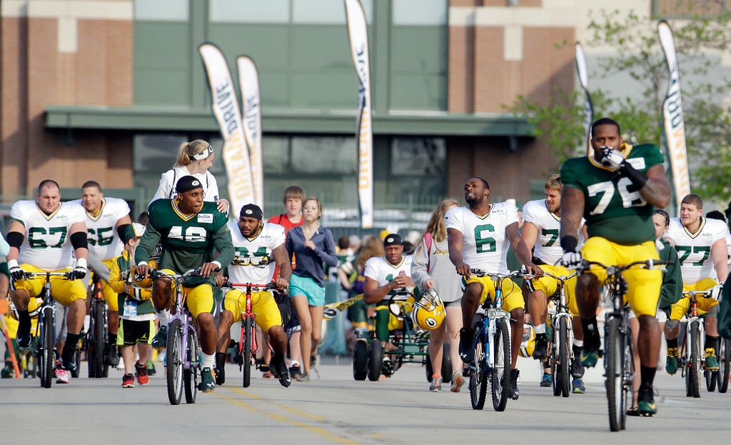 . Green Bay Packers players ride bikes to NFL football training camp Monday, July 28, 2014, in Green Bay, Wis. (AP Photo/Morry Gash)