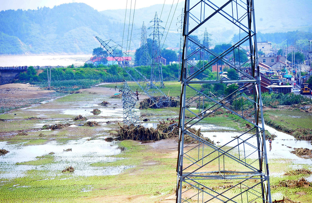 """. Damaged power transmission towers (C) leaning to the ground after being damaged by floods in the Qingyuan Manchu autonomous county of Fushun, in northeast China\'s Liaoning province on August 18, 2013. Devastating floods at opposite ends of China have left 105 people dead and another 115 missing in recent days, state media said on August 19. Flooding in the northeast which left 72 people dead was described as \""""the worst in decades\"""" by the state news agency, while another 33 people died in the south as a result of the weather, it said citing the ministry of civil affairs.   AFP PHOTOSTR/AFP/Getty Images"""