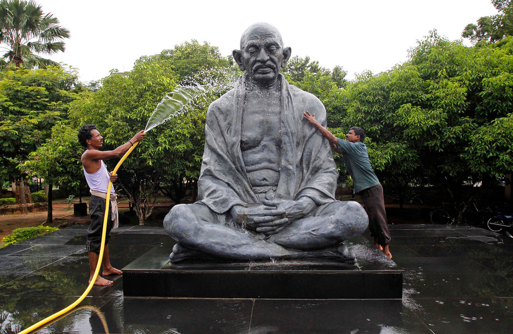 . Indians clean a statue of Mahatma Gandhi ahead of Gandhi Jayanti in Bhubaneswar, India, Tuesday, Oct. 1, 2013. Gandhi Jayanti is a national holiday in the country, marking the birth anniversary of Mahatma Gandhi. (AP Photo/Biswaranjan Rout)