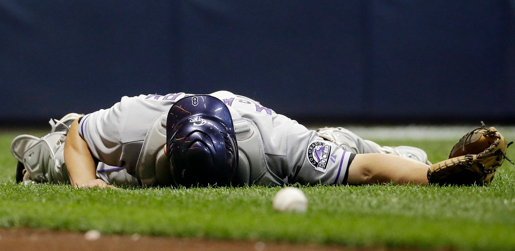 . Colorado Rockies catcher Michael McKenry lies on the ground after not catching a bunt foul by Milwaukee Brewers\' Martin Maldonado during the seventh inning of a baseball game Friday, June 27, 2014, in Milwaukee. (AP Photo/Morry Gash)