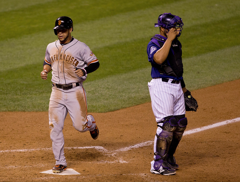 . DENVER, CO - AUGUST 27:  Gregor Blanco #7 of the San Francisco Giants crosses home plate as catcher Wilin Rosario #20 of the Colorado Rockies adjusts his mask during the seventh inning at Coors Field on August 27, 2013 in Denver, Colorado.  The Giants defeated the Rockies 5-3.  (Photo by Justin Edmonds/Getty Images)