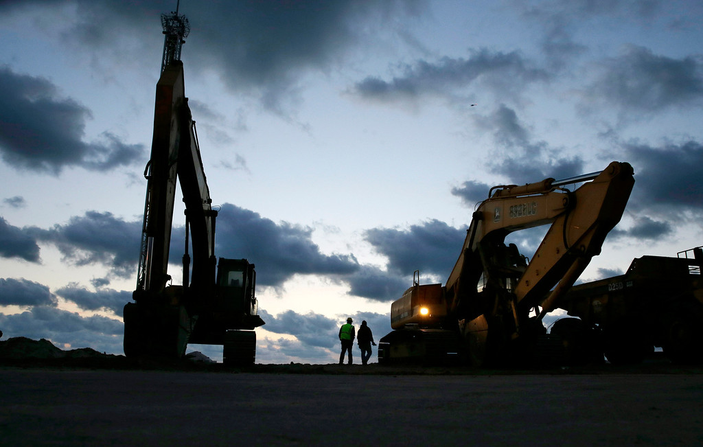 . In early morning darkness, workers prepare heavy machinery for the day as rebuilding work continues on the beach area of Seaside Heights and Seaside Park, N.J., Tuesday, Oct. 29, 2013. (AP Photo/Mel Evans)