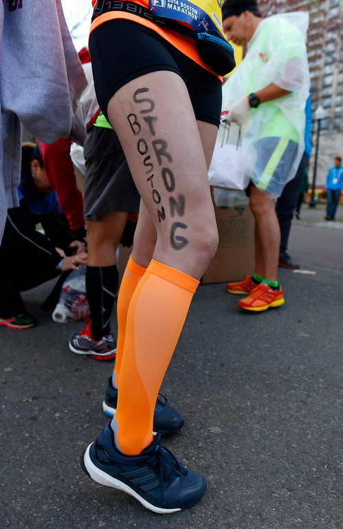 """. Kimberley Garcia of Boston poses with the slogan \""""Boston Strong\"""" on her leg in Boston before boarding a bus to the starting line in Hopkinton, Mass., to compete in  the 118th Boston Marathon Monday, April 21, 2014. (AP Photo/Matt Rourke)"""