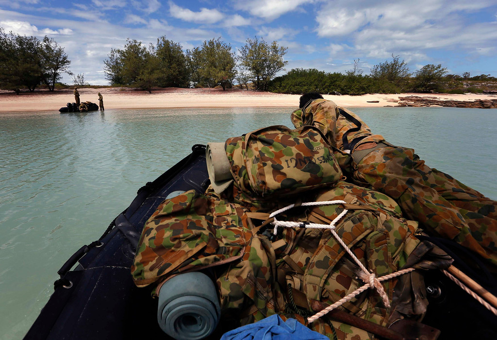 . An indigenous soldier from Australia\'s North West Mobile Force (NORFORCE) unit prepares to land his inflatable boat onto Wigram Island, part of the English Company Islands, located inside Arnhem Land in the Northern Territory, Australia July 17, 2013. NORFORCE is a surveillance unit that employs ancient Aboriginal skills to help in the seemingly impossible task of patrolling the country\'s vast northwest coast. NORFORCE\'s area of operations is about 1.8 million square km (700,000 square miles), covering the Northern Territory and the north of Western Australia. Aboriginal reservists make up a large proportion of the 600-strong unit, and bring to bear their knowledge of the land and the food it can provide. Fish, shellfish, turtle eggs and even insects supplement rations during the patrol, which is on the lookout for illegal foreign fishing vessels and drug smugglers, as well as people smugglers from  neighboring Indonesia.  Picture taken July 17, 2013. REUTERS/David Gray