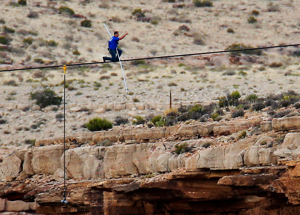 . Daredevil Nik Wallenda gives a thumbs-up sign as he nears the end, after walking on a two-inch (5-cm) diameter steel cable rigged 1,400 feet  (426.7 metres) across more than a quarter-mile deep remote section of the Grand Canyon near Little Colorado River, Arizona June 23, 2013.  REUTERS/Mike Blake