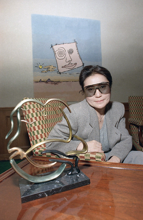 ". Yoko Ono, widow of John Lennon poses with one of his works entitled ""Bag One\""  at the opening of a show of previously unreleased Lennon art at a Chicago art gallery on Friday, Feb. 26, 1988 in Chicago.   The collection includes bronze sculpture, stone lithographs, serigraphs, tapestries, and kinetic neon sculpture. (AP Photo/Mark Elias)"