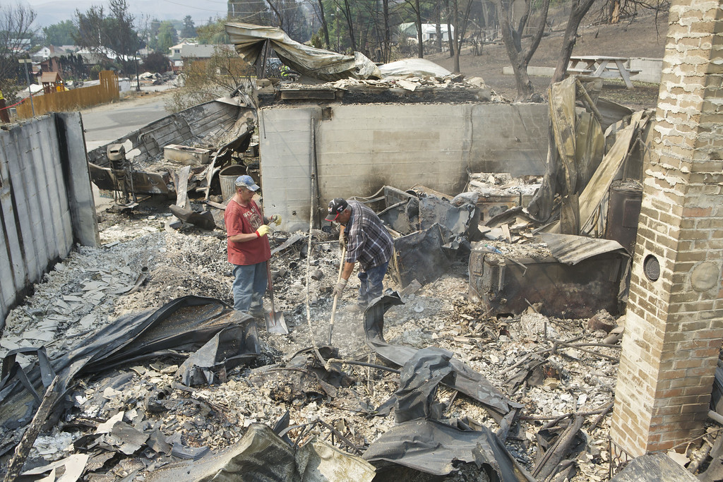 . Randy Loucks, right, of Brewster, Washington and Rich Pitkethly of Brewster dig through the remains of a home belonging to Loucks mother-in-law following a wildfire July 20, 2014 in Pateros, Washington. The home was destroyed in a fire storm July 17. Loucks had just finished sprucing up the house with new paint and carpet as a surprise to his mother-in-law, who is visiting relatives in Arkansas. Several fires throughout the state have destroyed hundreds of home forced evacuations and continue to threaten more communities. (Stephen Brashear/Getty Images)
