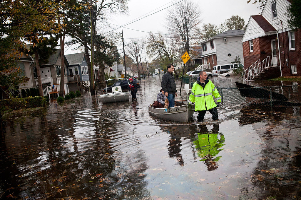 . An emergency responder helps evacuate two people with a boat after their neighborhood experienced flooding due to Hurricane Sandy, on October 30, 2012, in Little Ferry, New Jersey. The storm has claimed at least 16 lives in the United States, and has caused massive flooding across much of the Atlantic seaboard. US President Barack Obama has declared the situation a \'major disaster\' for large areas of the US East Coast including New York City. (Photo by Andrew Burton/Getty Images)