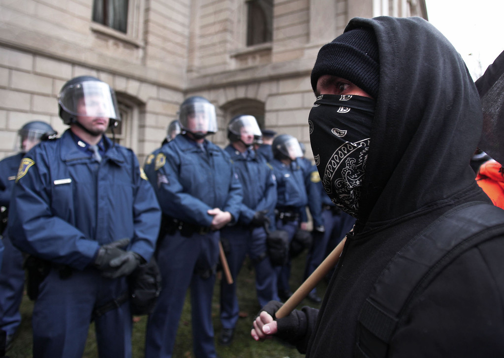 . A masked protester looks at Michigan State Police in riot gear as union members from around the country rally at the Michigan State Capitol to protest a vote on Right-to-Work legislation December 11, 2012 in Lansing, Michigan. Republicans control the Michigan House of Representatives, and Michigan Gov. Rick Snyder has said he will sign the bill if it is passed. The new law would make requiring financial support of a union as a condition of employment illegal. (Photo by Bill Pugliano/Getty Images)