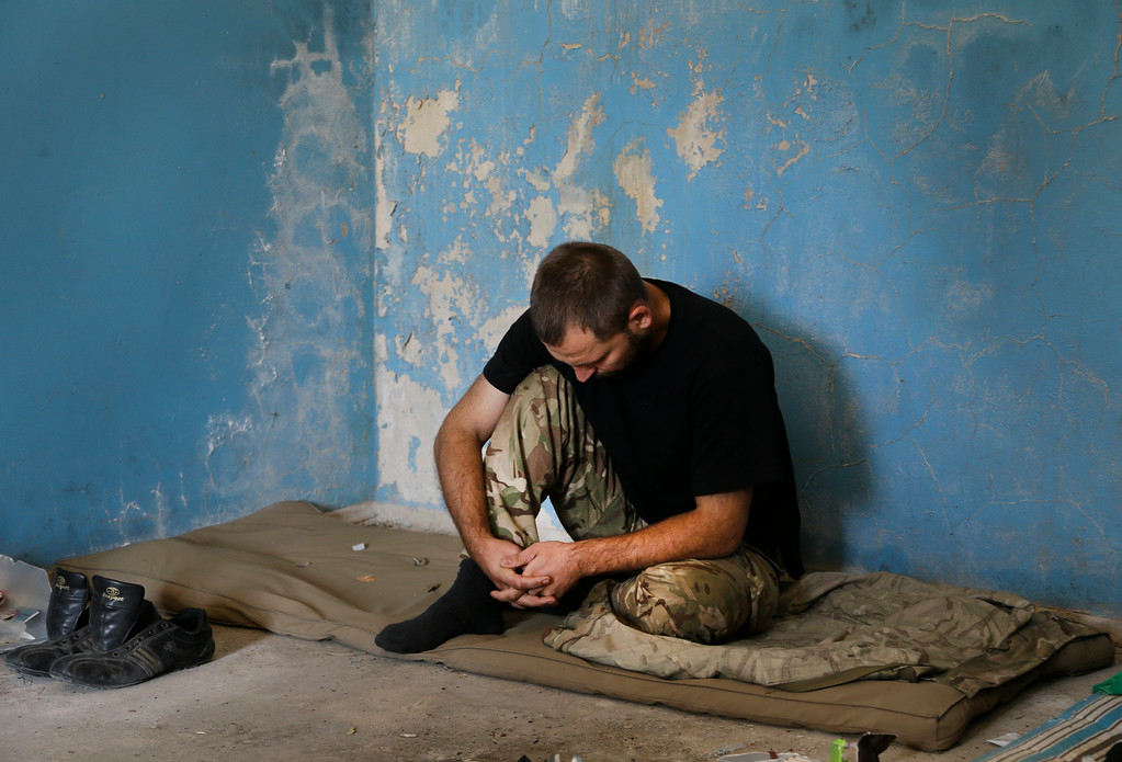 . Captured Ukrainian border guard sits in a  garage at the Novoazovsk border crossing point, in eastern Ukraine, Friday, Aug. 29, 2014. In Novoazovsk, pro Russian rebel fighters looked to be in firm control, well-equipped and relaxed. At least half a dozen tanks were seen on roads around the town, although the total number at the rebelsí disposal is believed to be much greater. Novoazovsk fell swiftly to the rebels Wednesday after being pounded by shelling. (AP Photo/Sergei Grits)