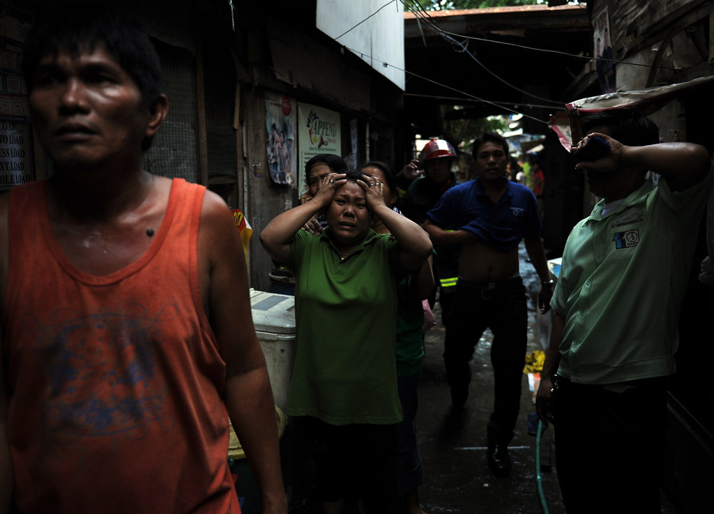 . Residents react as fire engulfs a shanty town at the financial district of Manila on July 11, 2013, leaving more than 1,000 people homeless according to city officials. There were no immediate reports of casualties from the blaze, which occurred mid-morning amid government plans to relocate thousands of families living in areas vulnerable to floods and typhoons. TED ALJIBE/AFP/Getty Images
