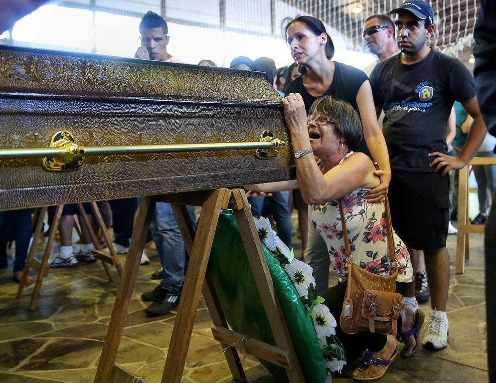 . Relatives of victims from a fire that broke out at a nightclub weep, during their funeral in Santa Maria, 550 Km from Porto Alegre, southern Brazil on January 27, 2013. At least 232 people died and 131 were injured early Sunday when a fire tore through a nightclub packed with university students in the southern Brazilian city of Santa Maria, police said.  JEFFERSON BERNARDES/AFP/Getty Images