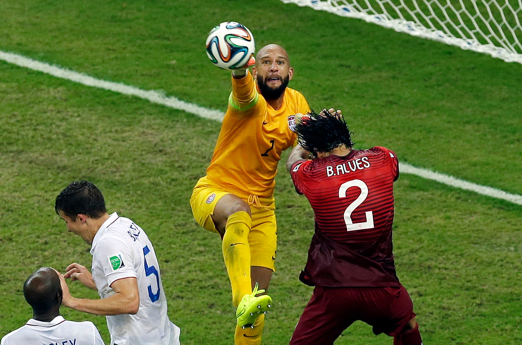 . United States\' goalkeeper Tim Howard, center, reaches a ball ahead of Portugal\'s Bruno Alves, right, during the group G World Cup soccer match between the USA and Portugal at the Arena da Amazonia in Manaus, Brazil, Sunday, June 22, 2014. (AP Photo/Themba Hadebe)