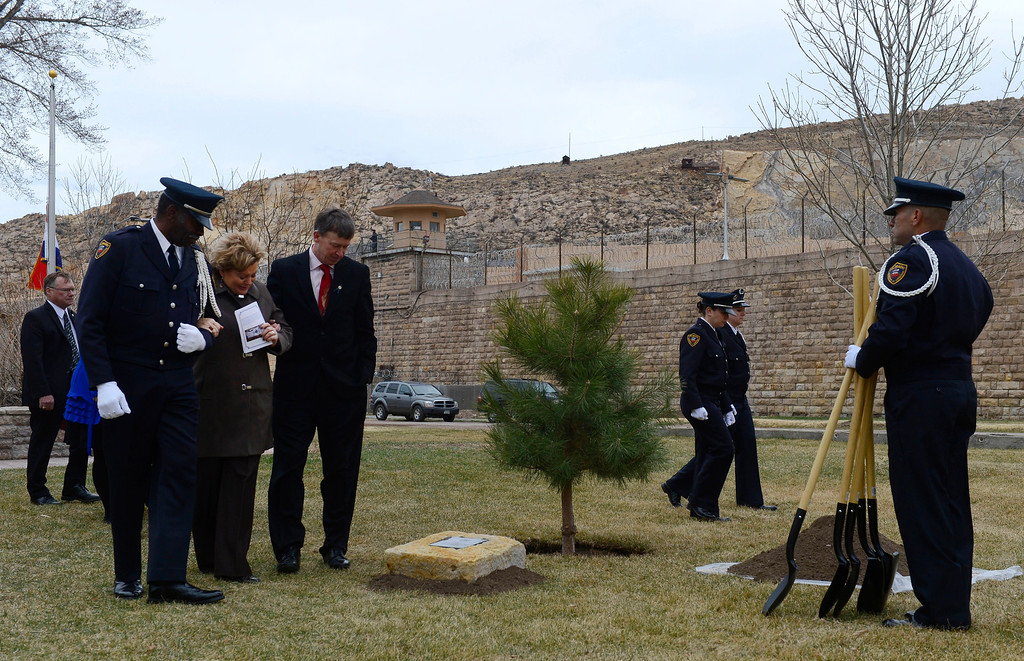 . Colorado Department of Corrections Honor Guard member, Harry Campbell, left, along with Colorado Governor, John Hickenlooper, right, escort Lisa Clements, center, to a tree dedicated to her fallen husband, Tom Clements at the Colorado Department of Corrections Fallen Officer Memorial  at the Territorial Correctional Facility park Saturday morning, March 15, 2014.  (Photo By Andy Cross / The Denver Post)