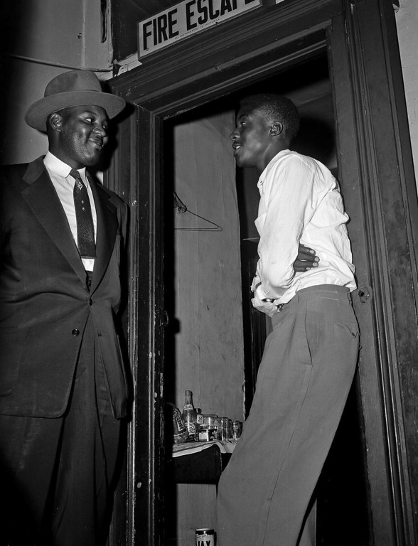 . Willie Reed, right, a witness in the Emmett Till murder case in Mississippi, stands outside the door of his apartment in Chicago under guard by Detective Sherman Smith. Reed, who changed his name to Willie Louis and told no one of his connection to the case, not even his future wife, was brought to Chicago by friends after his testimony in the trial.  His wife, Juliet Louis said Wednesday, July 24, 2013, that her husband died July 18, 2013 at a hospital in Oak Lawn, Ill. He was 76.  (AP Photo/Charles Knoblock, File)