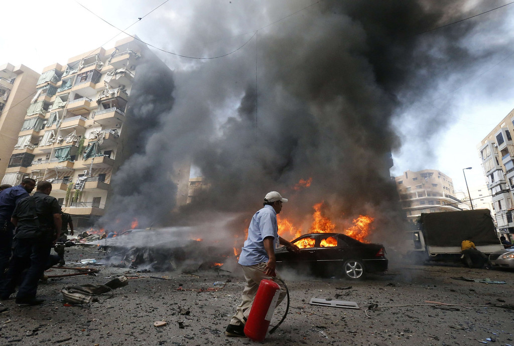 . Firefighters extinguish fire at the site of an explosion in Beirut\'s southern suburb neighborhood of Bir al-Abed on July 9, 2013.  AFP PHOTO/STR-/AFP/Getty Images