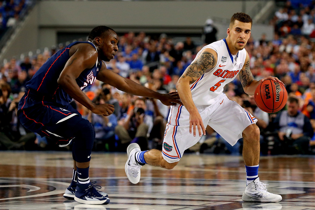 . ARLINGTON, TX - APRIL 05: Scottie Wilbekin #5 of the Florida Gators drives to the basket as Terrence Samuel #3 of the Connecticut Huskies defends during the NCAA Men\'s Final Four Semifinal at AT&T Stadium on April 5, 2014 in Arlington, Texas.  (Photo by Ronald Martinez/Getty Images)