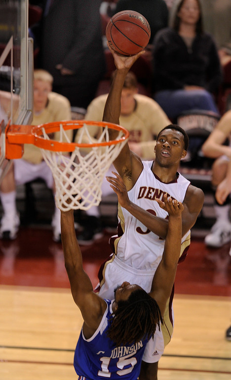 . Pioneers forward Chris Udofia (34) put up a shot over Bulldogs guard Cordarius Johnson (15) in the second half. The University of Denver men\'s basketball team defeated the Louisiana Tech Bulldogs 78-54 at Magness Arena Saturday night, March 9, 2013. (Photo By Karl Gehring/The Denver Post)