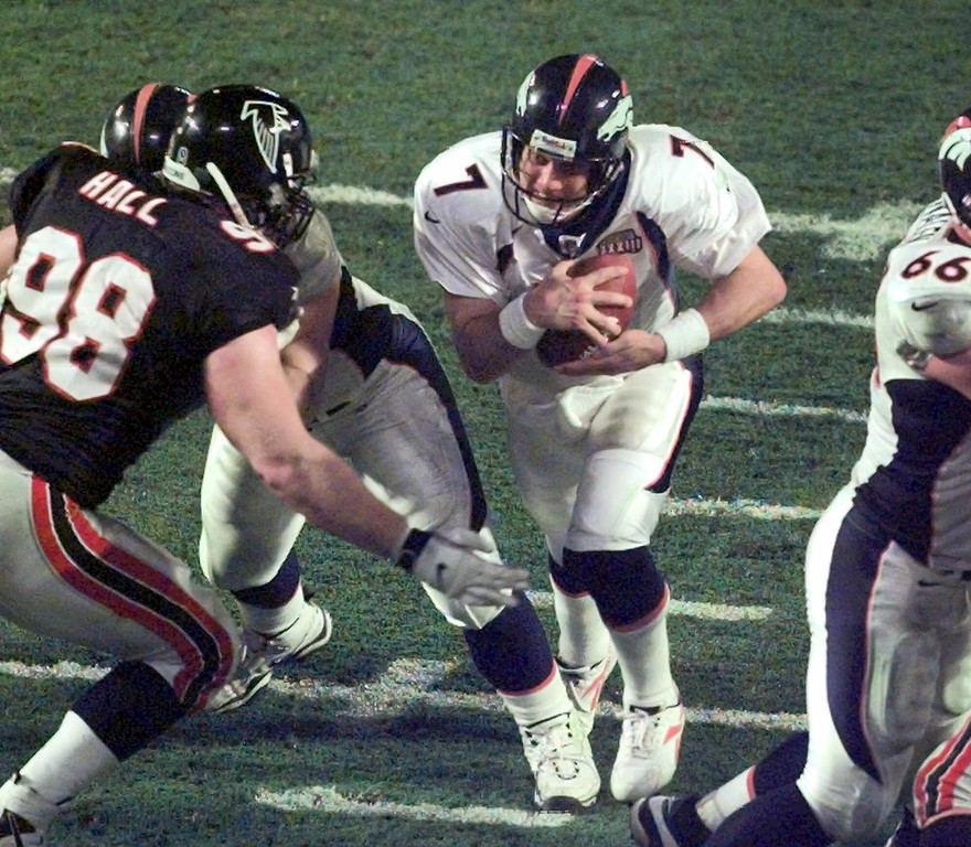 . Denver Broncos quarterback John Elway runs through a hole in the Atlanta Falcons line to score in the fourth quarter of Super Bowl XXXIII in Miami, Sunday, Jan. 31, 1999. At left is Falcons defensive tackle Travis Hall. (AP Photo/Wilfredo Lee)