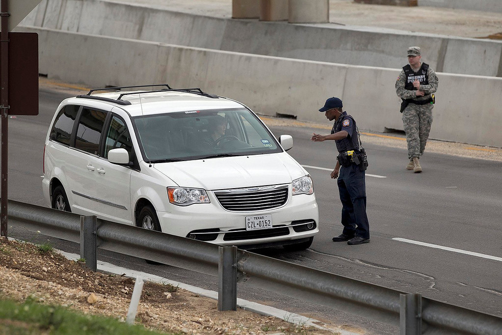 . Vehicles are checked outside of the Bernie Beck Gate, Wednesday, April 2, 2014, in Fort Hood, Texas. At least one person was killed and 14 injured in a shooting at Fort Hood, and officials at the base said the shooter is believed to be dead. (AP Photo/American-Statesman, Deborah Cannon)