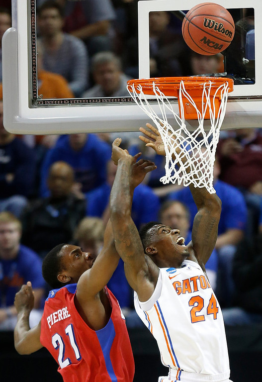 . Florida forward Casey Prather (24) looks at a shot ball as Dayton forward Dyshawn Pierre (21) defends during the first half in a regional final game at the NCAA college basketball tournament, Saturday, March 29, 2014, in Memphis, Tenn. (AP Photo/John Bazemore)