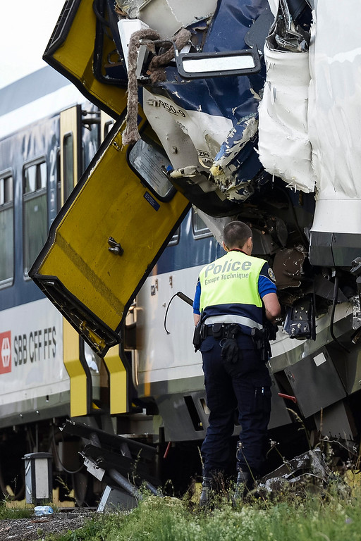 . A police officer works at the site where two passenger trains collided head-on in Granges-pres-Marnand, western Switzerland, Monday, July 29, 2013. Police says that 44 people have been injured.  (AP Photo/Keystone, Laurent Gillieron)