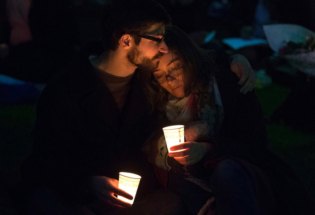 . A couple embrace while taking part in a candlelight vigil for bomb victims a day after two explosions hit the Boston Marathon, in Boston, Massachusetts April 16, 2013. The twin blasts on Monday killed three people including an 8-year-old boy and injured 176 others, some of whom were maimed by bombs packed with ball bearings and nails.  REUTERS/Adrees Latif