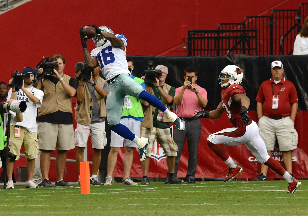 . GLENDALE, AZ - AUGUST 17:  Tim Benford #18 of the Dallas Cowboys makes a leaping catch while being defended by Jamell Fleming #23 of the Arizona Cardinals at University of Phoenix Stadium on August 17, 2013 in Glendale, Arizona.  (Photo by Norm Hall/Getty Images)