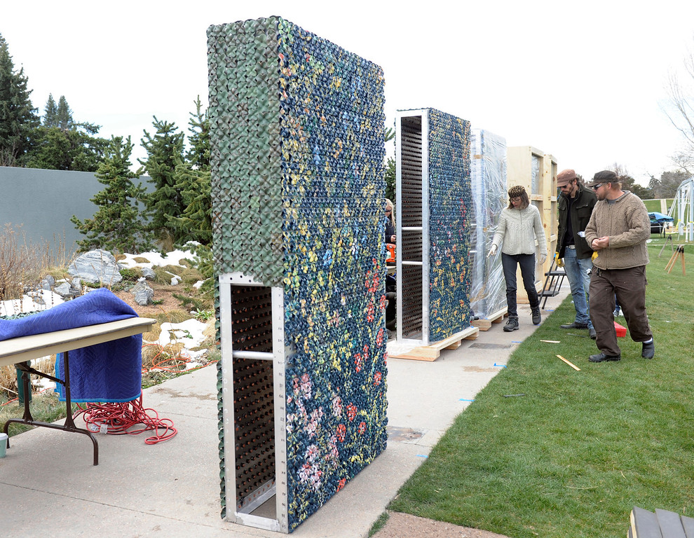 . Artist Kim Dickey, left, watches as volunteers help unwrap her 20 foot ceramic wall covered in ceramic flowers. Artists and volunteers work on a new art installation, Catalyst: Colorado Sculpture at the Denver Botanic Gardens.  (Photo By Kathryn Scott Osler/The Denver Post)