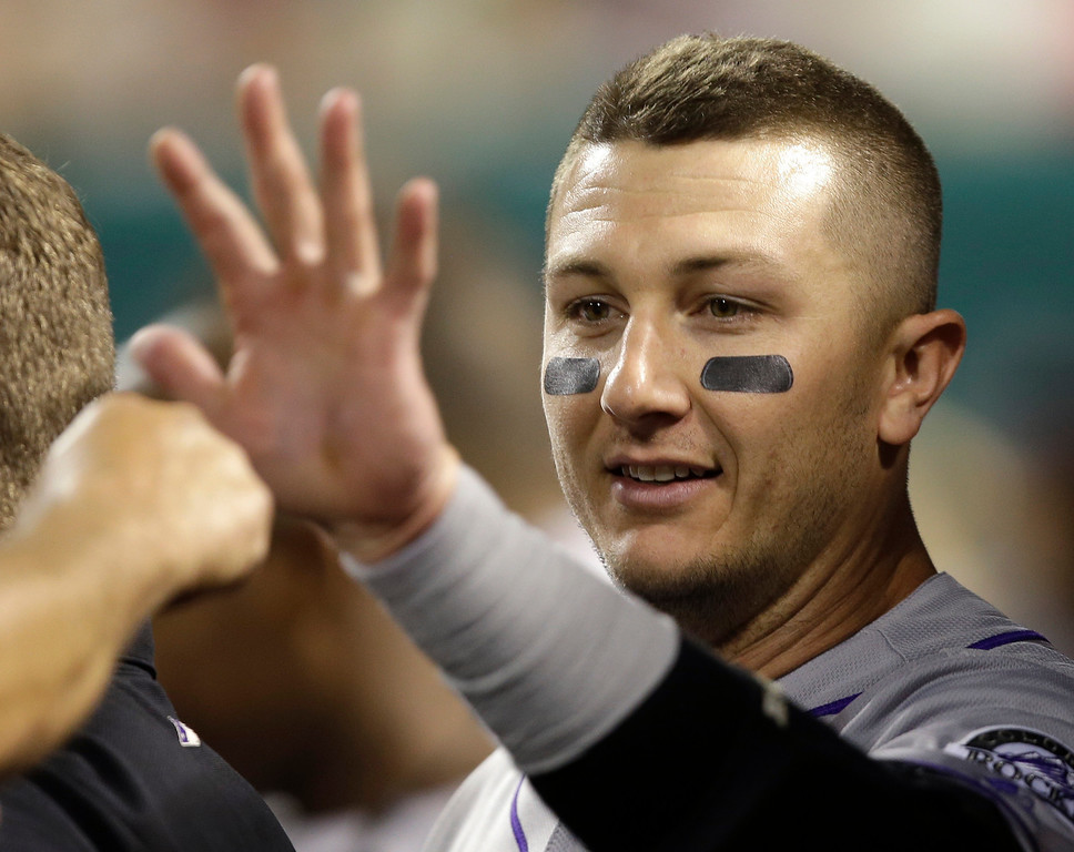 . Colorado Rockies\' Troy Tulowitzki is congratulated in the dugout after hitting a two-run home run off Cincinnati Reds relief pitcher Sam LeCure in the eighth inning of a baseball game, Tuesday, June 4, 2013, in Cincinnati. Colorado won 5-4. (AP Photo/Al Behrman)