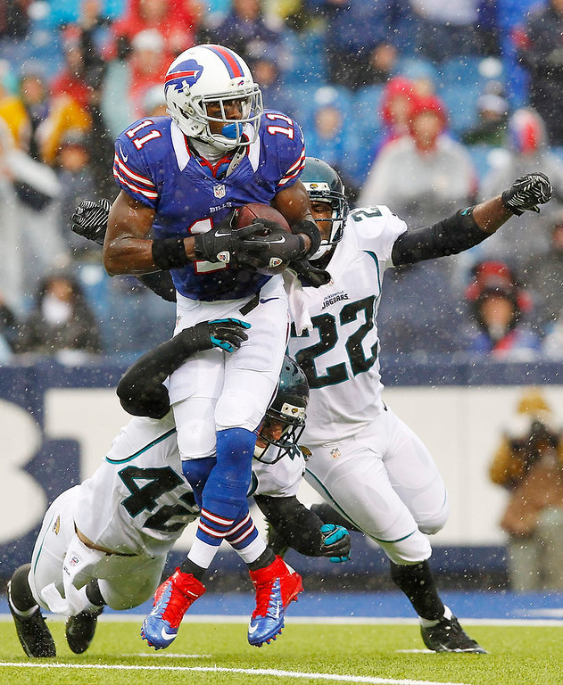 . Buffalo Bills\' T.J. Graham (11) catches a pass as he is defended by Jacksonville Jaguars\' Chris Prosinski (42) and Kevin Rutland (22) during the first half of an NFL football game Sunday, Dec. 2, 2012 in Orchard Park, N.Y. (AP Photo/Bill Wippert)