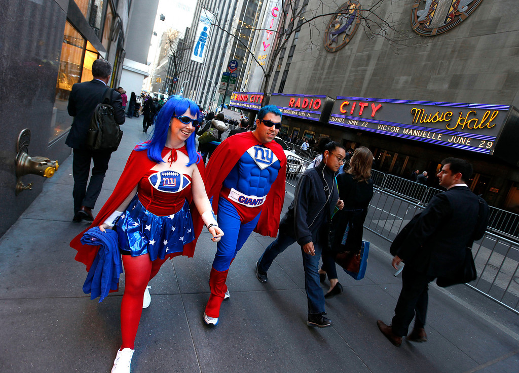 . New York Giants fans Eric Maybee and Kathleen O\'Connor walk outside Radio City Music Hall before the first round of the NFL football draft on Thursday, April 25, 2013, in New York. (AP Photo/Jason DeCrow)