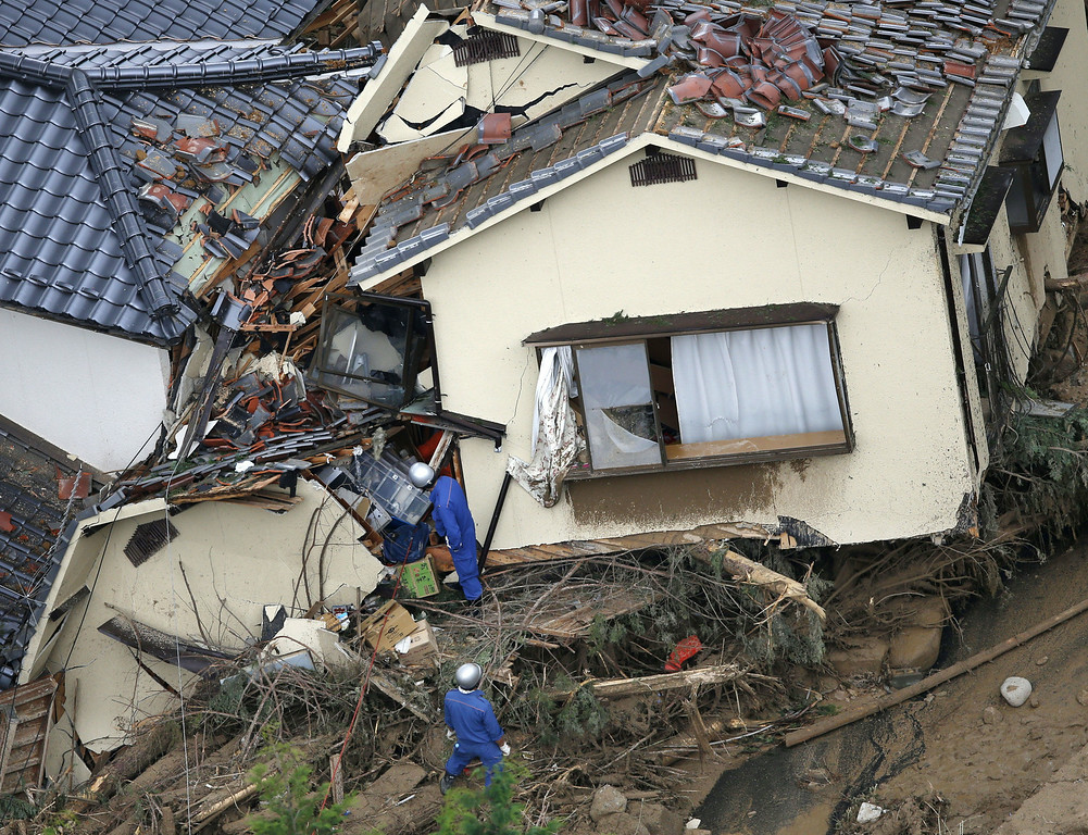 . In this aerial photo, rescue workers search for survivors in an area devastated by a massive landslide which swept through residential areas in Hiroshima, western Japan, Wednesday, Aug. 20, 2014. (AP Photo/Kyodo News)