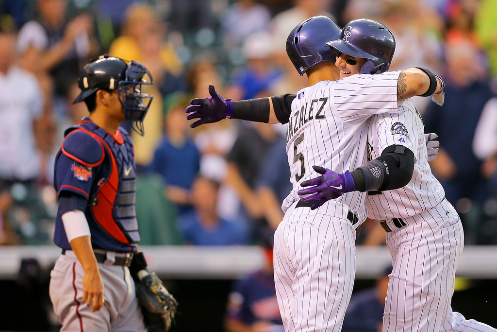 . DENVER, CO - JULY 11: Troy Tulowitzki #2 of the Colorado Rockies celebrates his two run home run with Carlos Gonzalez #5 as Kurt Suzuki #8 of the Minnesota Twins looks on during the third inning at Coors Field on July 11, 2014 in Denver, Colorado. (Photo by Justin Edmonds/Getty Images)