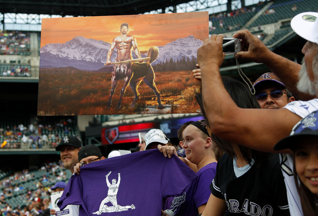 . Fans take photographs of a painting, top, in the likeness of Colorado Rockies first baseman Todd Helton before the Rockies face the Arizona Diamondbacks in the first inning of a baseball game in Denver on Sunday, Sept. 22, 2013. Helton is retiring at season\'s end after 17 years at first base for the Rockies. (AP Photo/David Zalubowski)