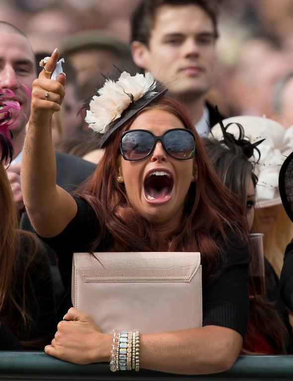 . A racegoer cheers on her horse during Ladies\' Day at Aintree Racecourse Liverpool, England, Friday, April 5, 2013. (AP Photo/Jon Super)