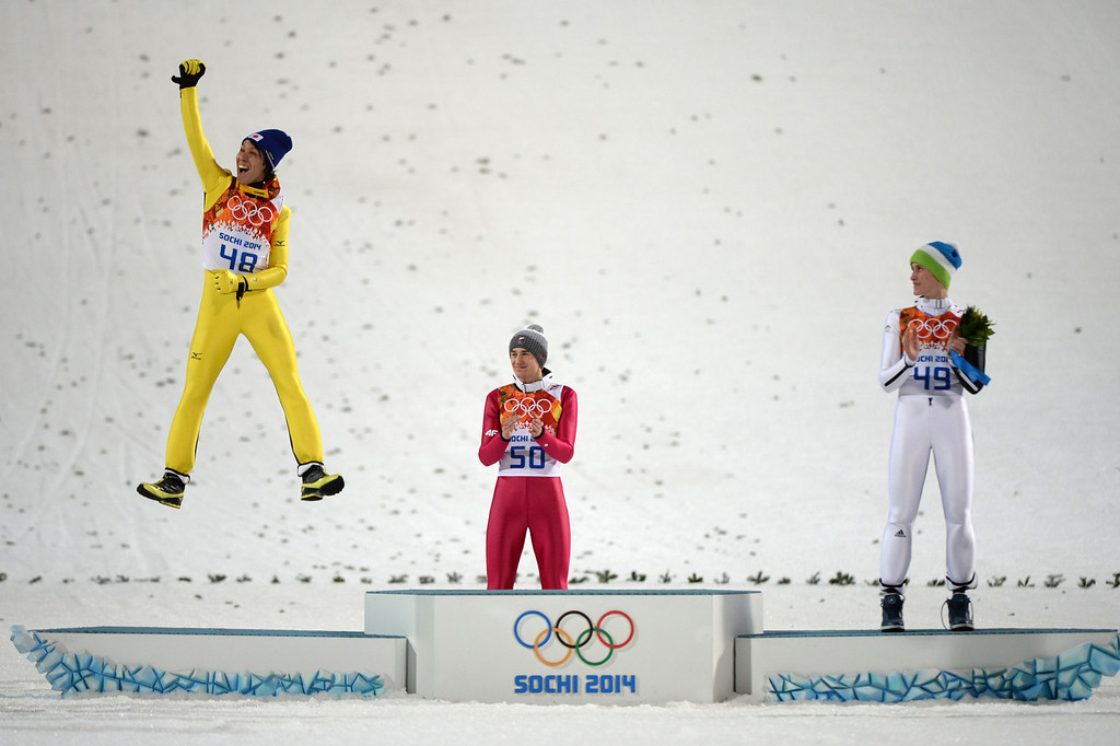 . (LtoR) Silver winner Japan\'s Noriaki Kasai jumps next to gold winner Poland\'s Kamil Stoch and bronze medalist Slovenia\'s Peter Prevc to celebrate on the podium during the Men\'s Ski Jumping Large Hill Individual Flower Ceremony at the RusSki Gorki Jumping Center during the Sochi Winter Olympics on February 15, 2014, in Rosa Khutor.  PETER PARKS/AFP/Getty Images