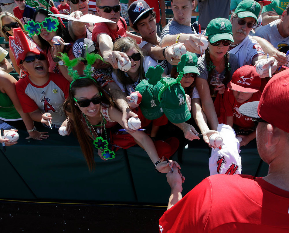 . Fans dressed up for St. Patrick\'s Day try for an autograph from Los Angeles Angels left fielder Mark Trumbo before a spring training baseball game against the San Diego Padres in Tempe, Ariz., Sunday, March 17, 2013. (AP Photo/Chris Carlson)