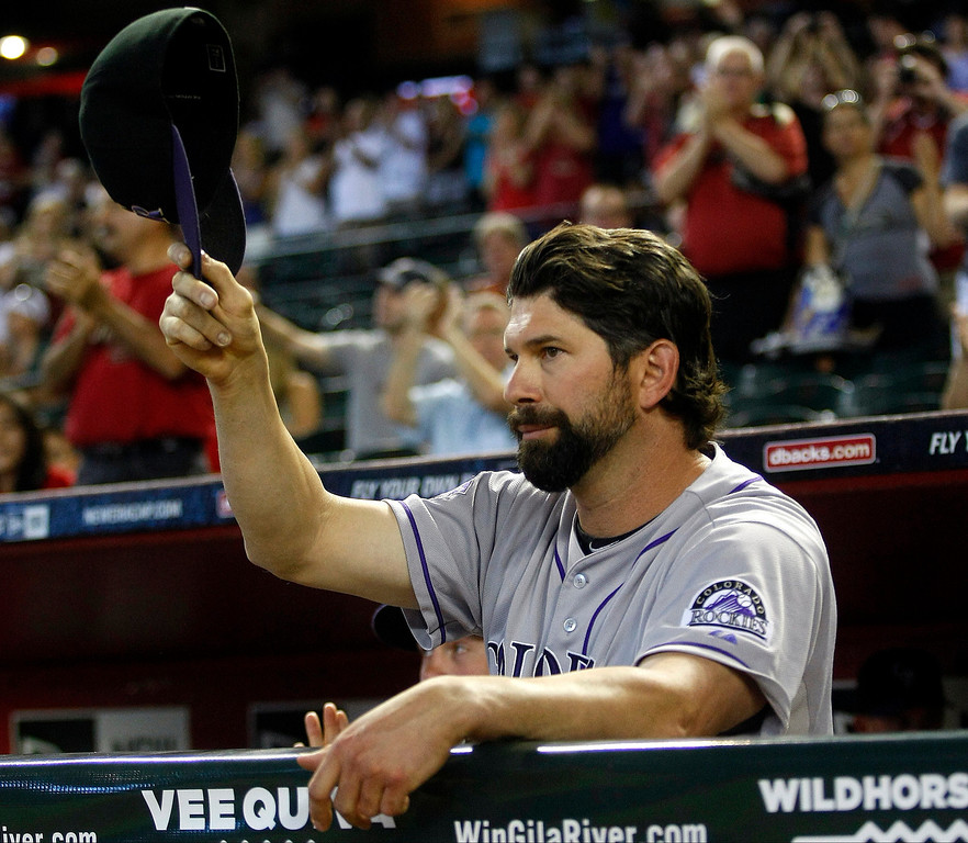 . Colorado Rockies first baseman Todd Helton acknowledges the crowd in the second inning after announcing his retirement at the end of the season during a baseball game against the Arizona Diamondbacks, Sunday, Sept. 15, 2013, in Phoenix. (AP Photo/Rick Scuteri)