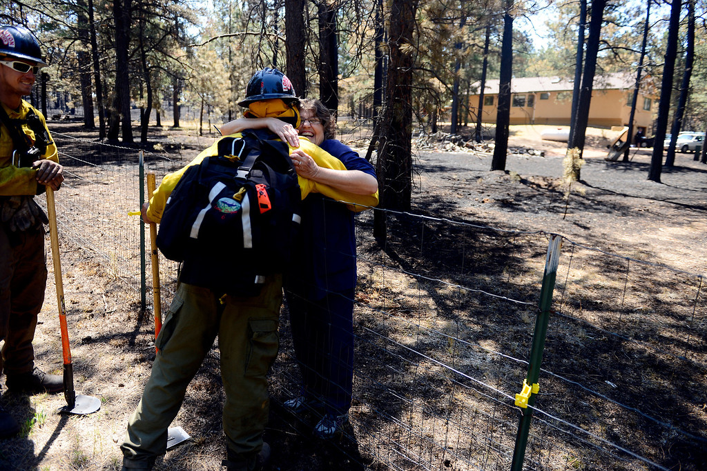 . BLACK FOREST, CO - JUNE 19: Long Canyon Wildland firefighter Lynn Reynolds is hugged by homeowner Jody Wallace as he and his crew coal trail at a burned property on Pine Glen Drive. Only one home on the loop of Pine Glen Drive burned in the fire and Wallace wanted to personally thank a fire crew for saving her adjacent home. (Photo by AAron Ontiveroz/The Denver Post)